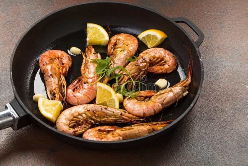 De garnalengarnalen met knoflook, citroen, kruiden en Italiaanse peterselie versieren in een zwarte pan op witte geschilderde rus royalty-vrije stock afbeelding