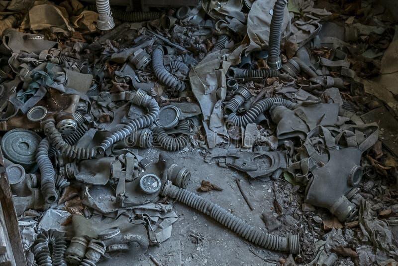 De gasmaskers van vele kinderen spreiden in het klaslokaal van verlaten school uit stock afbeelding