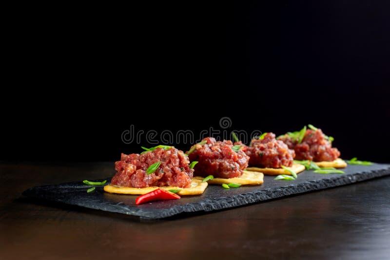 De gastronomische aanzet van het delicatesse ruwe vlees op zwarte lei-2 royalty-vrije stock foto's