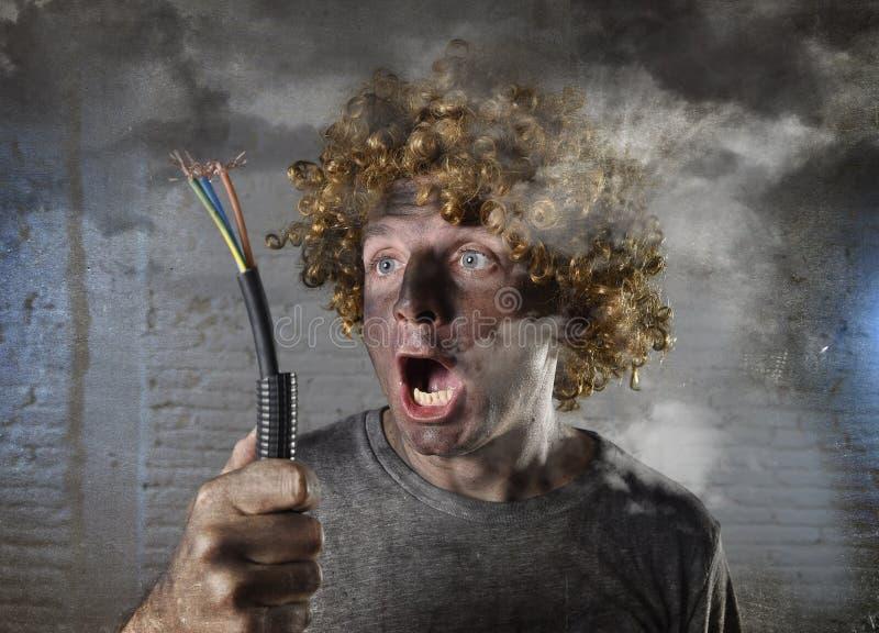 De geëlektrokuteerde mens met kabel die na binnenlands ongeval met vuile gebrande gezichtsschok roken elektrokuteerde uitdrukking royalty-vrije stock foto's