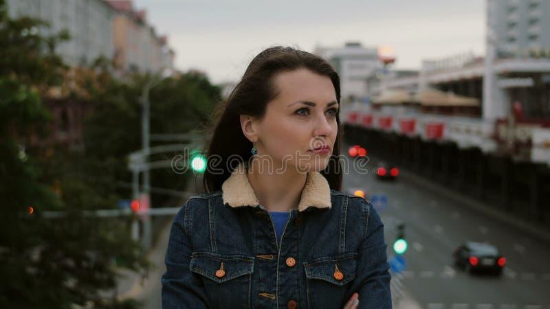 De geërgerde meisje status op brug drukt haar ontevredenheid, frustratie negatieve emoties uit en bekijkt de camera 4K stock fotografie