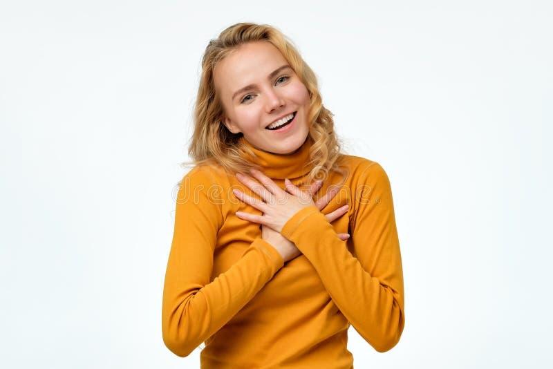 De geïmponeerde vriendschappelijke vrouw houdt handen op borst, die door compliment wordt geraakt, glimlachen royalty-vrije stock foto's