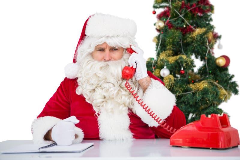 De geïrriteerde Kerstman op de telefoon stock afbeeldingen