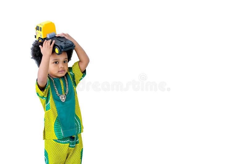 De geïsoleerde Afrikaanse jonge jongen houdt geel vrachtwagenstuk speelgoed over zijn hoofd met witte achtergrond stock fotografie