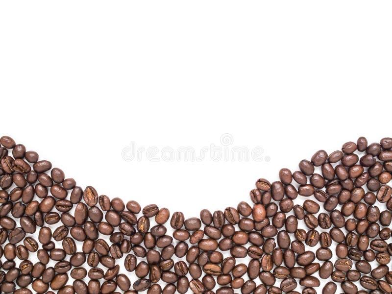 De geïsoleerde koffiebonen schikken bij de bodem in de vorm van de krommelijn royalty-vrije stock afbeelding