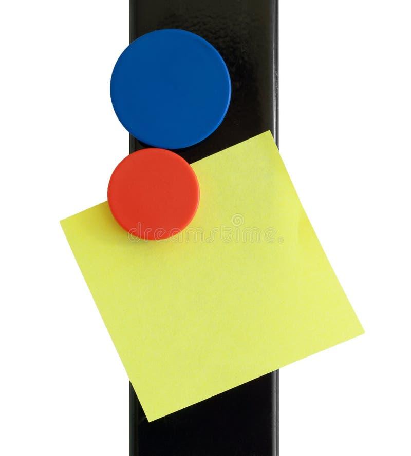 De geïsoleerde nota van de post-it over magnetische streep stock foto