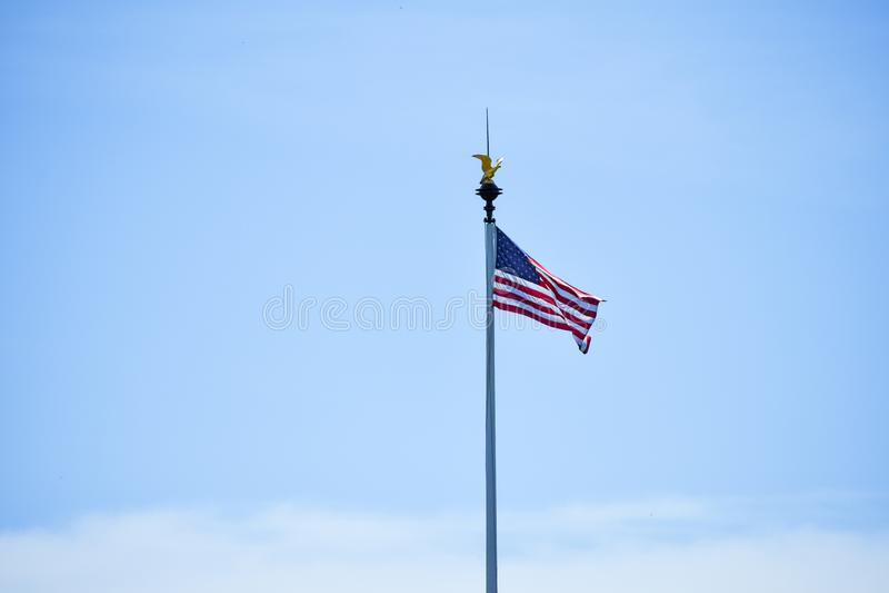 De geïsoleerde vlag die van Verenigde Staten in de wind op een blauwe hemelachtergrond golven Exemplaarruimte voor tekst stock foto