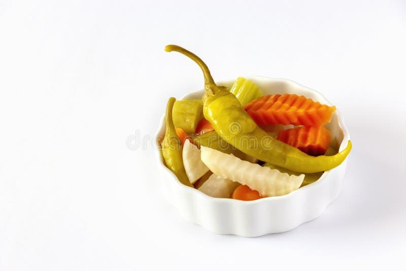 De geassorteerde wortel van groenten in het zuurgroenten, Spaanse peper, radijs in witte ceramische kom Hoogste mening Ge?soleerd royalty-vrije stock afbeelding