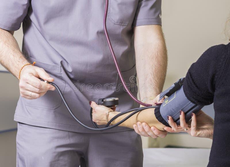 De gebaarde arts die glazen dragen controleert de de bloeddruk en impuls van de patiënt stock fotografie
