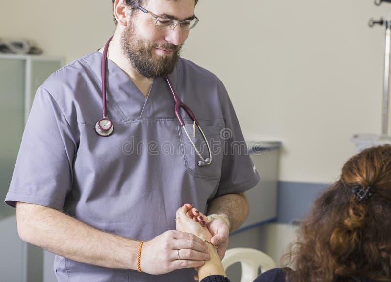 De gebaarde arts die glazen dragen controleert de impuls van de patiënt stock foto