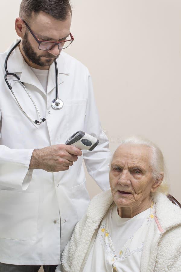 De gebaarde arts in een witte laag met een stethoscoop rond zijn hals meet de temperatuur van een zeer oude grijze vrouw met een  royalty-vrije stock foto's