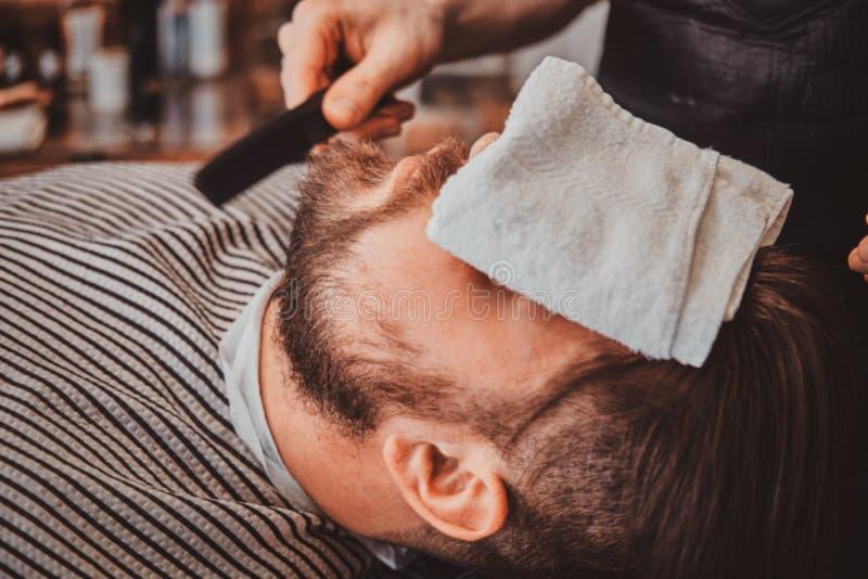 De gebaarde cliënt werd enkel goede beardcare van in kapper stock afbeelding