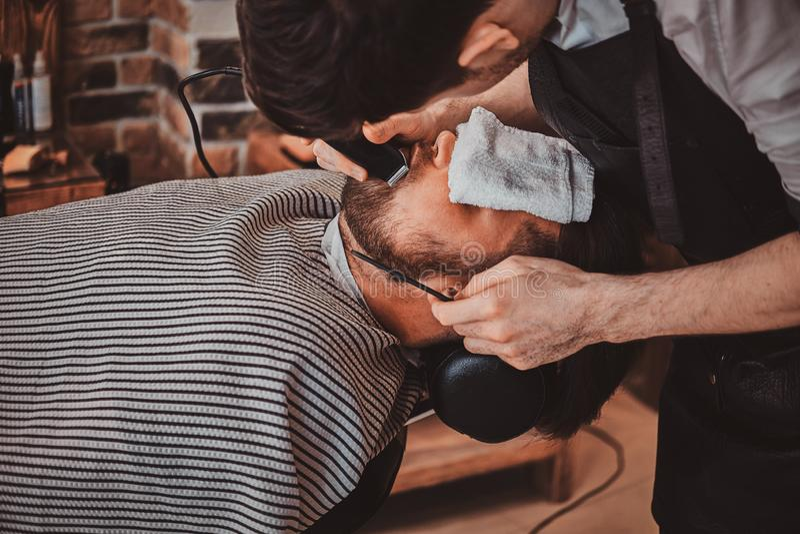 De gebaarde cliënt werd enkel goede beardcare van in kapper royalty-vrije stock fotografie
