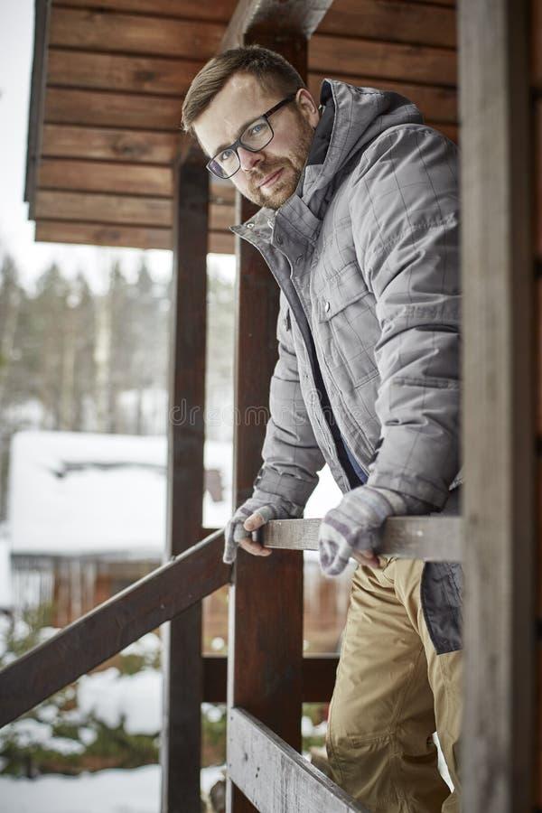 De gebaarde glimlachende mens met glazen en warme kleding die zich op de portiek van een blokhuis met van hem bevinden dient hand stock afbeeldingen