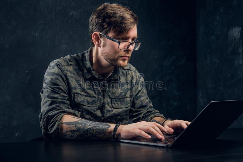 De gebaarde hakker in glazen maakt het binnendringen in een beveiligd computersysteem zitting achter laptop stock foto's