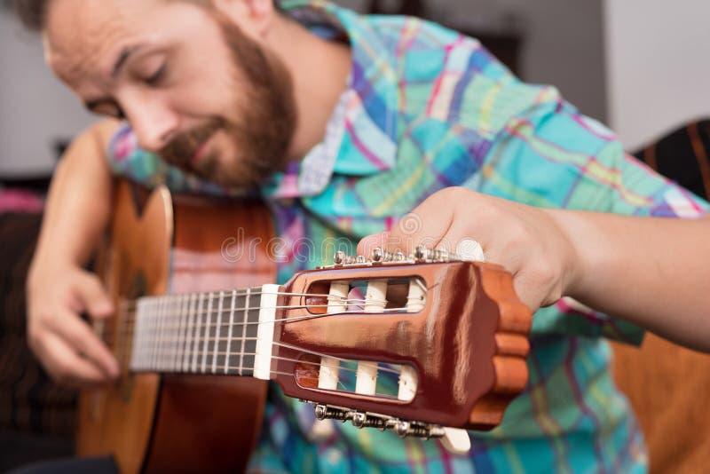 De gebaarde hand die van de hipstermens akoestische gitaar aanpassen Close-up selectieve nadruk op hand royalty-vrije stock foto's