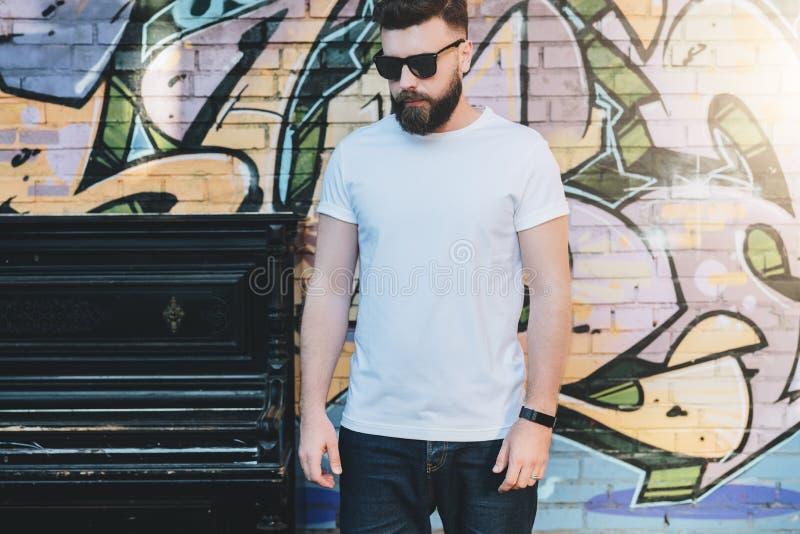 De gebaarde hipstermens gekleed in witte t-shirt is tribunes tegen muur met graffiti Spot omhoog Ruimte voor embleem, tekst, beel royalty-vrije stock afbeeldingen