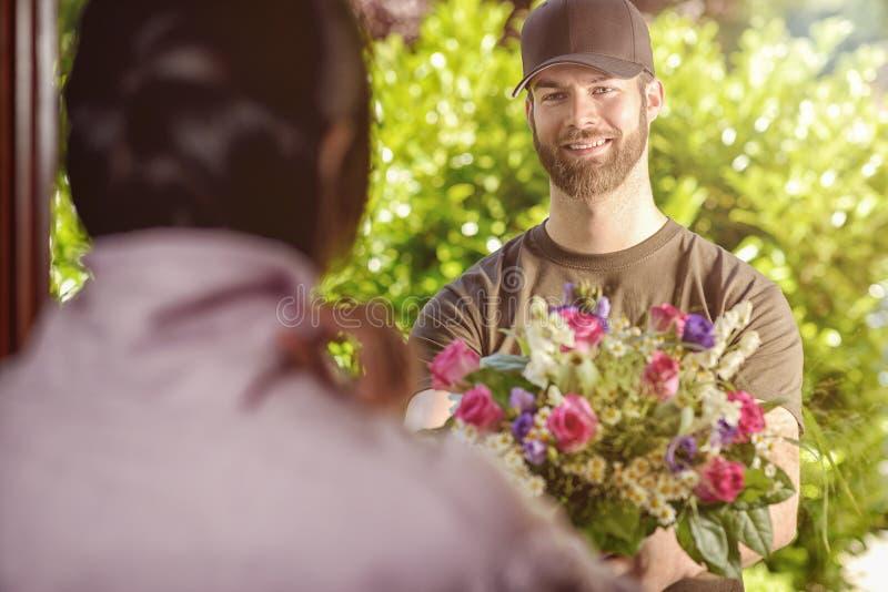 De gebaarde jaren '20man levert bloemen aan jonge vrouw stock fotografie