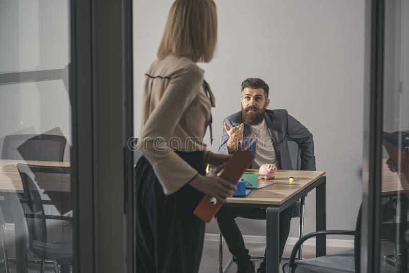 De gebaarde man en de vrouw hebben commerciële vergadering Gebaarde mensenbespreking aan secretaresse in bureau, mededeling en sa royalty-vrije stock afbeelding