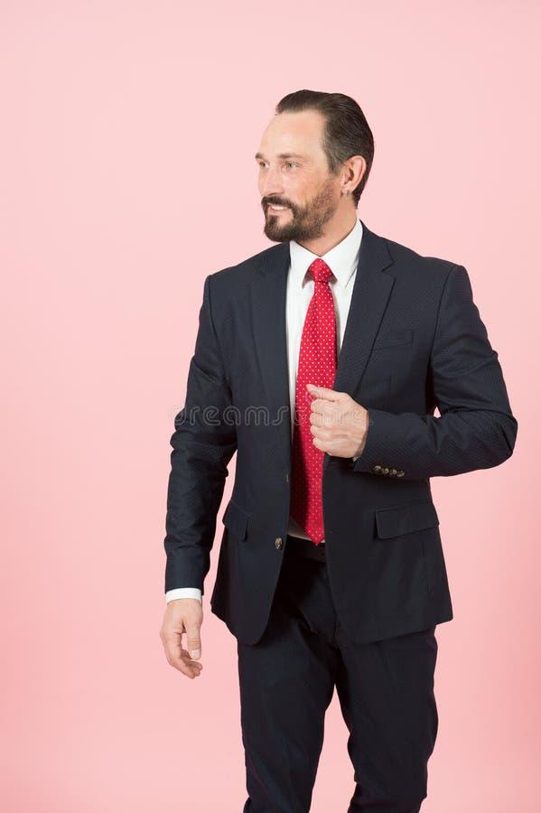 De gebaarde manager houdt hand op klep van blauw kostuumjasje die rode band op wit die overhemd dragen over roze achtergrond word royalty-vrije stock foto's