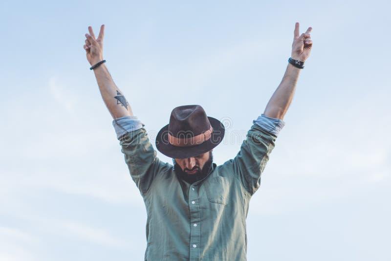 De gebaarde mannelijke dragende de manierhoed van Hipster, genietend van mening van blauwe en duidelijke hemel met hief zijn hand royalty-vrije stock foto