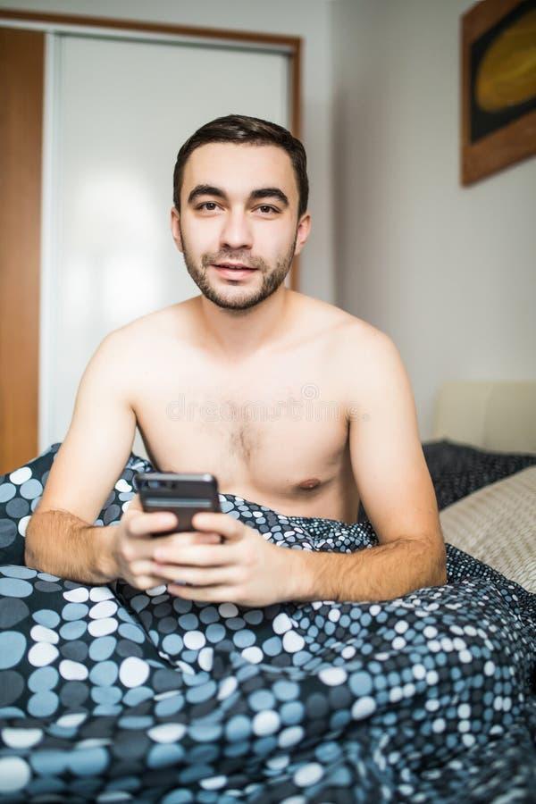 De gebaarde mens die in ochtendbed liggen met telefoon gebruikend app of lezend nieuws voedt royalty-vrije stock fotografie