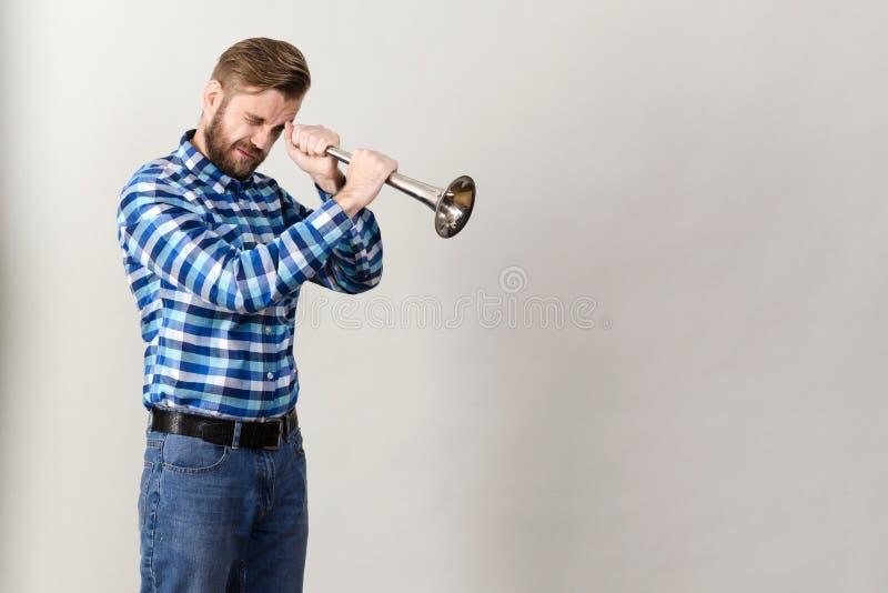 De gebaarde mens in een plaidoverhemd bekijkt de hoorn stock afbeeldingen