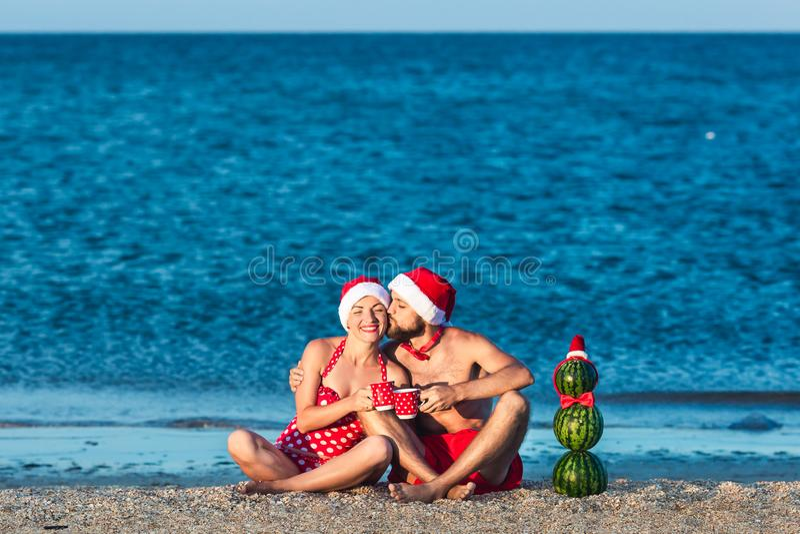 De gebaarde mens en het meisje in Kerstmankleren kussen op overzees strand met koppen in hun handen en sneeuwman van watermeloene stock afbeelding