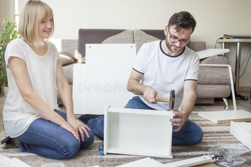 De gebaarde mens in glazen, een witte T-shirt en jeans zit op een tapijt in de woonkamer en verdraait meubilair Hij houdt de hame royalty-vrije stock foto's
