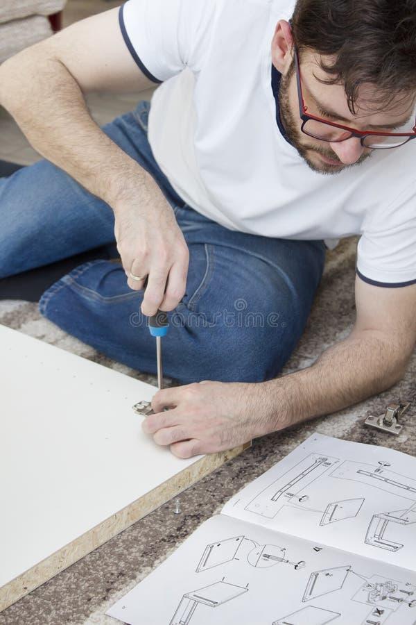 De gebaarde mens in glazen, een witte T-shirt en jeans zit op een tapijt in de woonkamer en verdraait meubilair Hij houdt de hame stock afbeelding