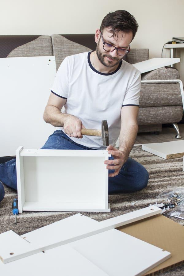 De gebaarde mens in glazen, een witte T-shirt en jeans zit op een tapijt in de woonkamer en verdraait meubilair Hij houdt de hame royalty-vrije stock afbeelding