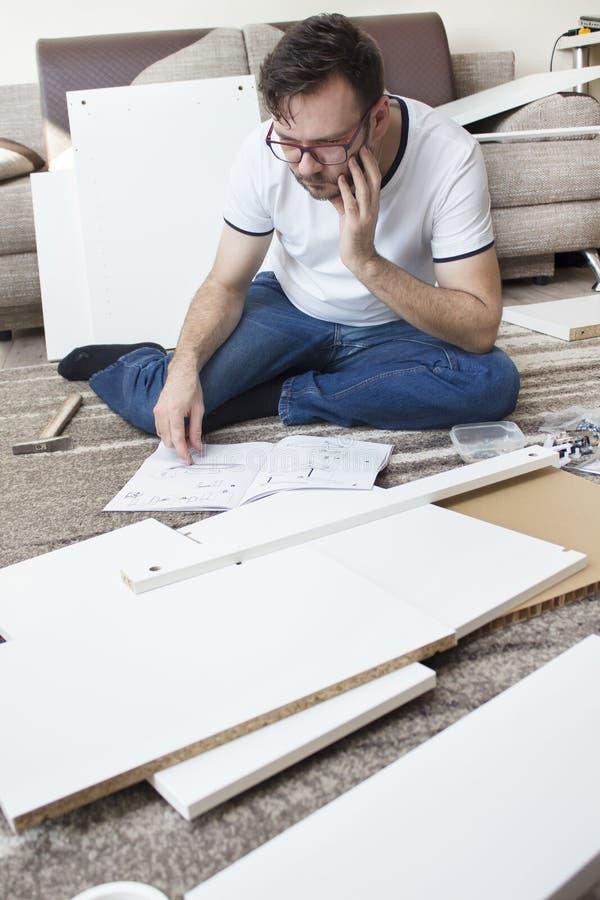 De gebaarde mens in glazen, een witte T-shirt en jeans zit zorgvuldig op de deken en leest de instructies van de meubilairassembl royalty-vrije stock afbeeldingen