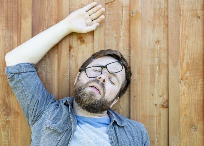 De gebaarde mens in glazen was vermoeid, bepaalt om op de houten vloer te rusten en fell in slaap met zijn open mond, in grappig  royalty-vrije stock fotografie
