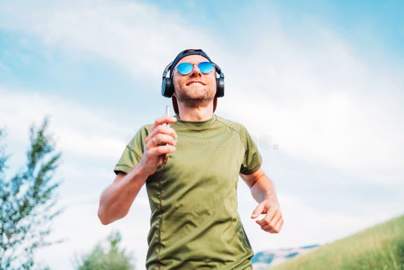 De gebaarde mens in honkbal GLB, de draadloze hoofdtelefoons en de blauwe zonnebril vrolijke het glimlachen lopende avond lopen t royalty-vrije stock foto's