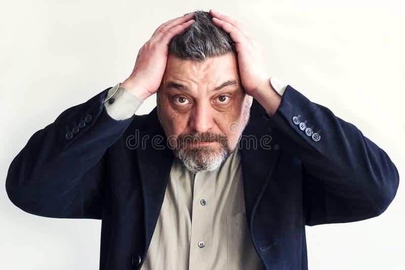 De gebaarde mens houdt zijn hoofd met beide handen problemen Gebrek aan tijd Ga niet zaken stock afbeeldingen