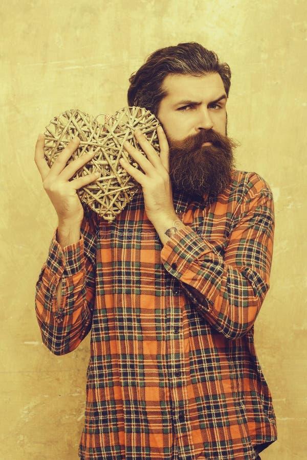 De gebaarde mens met lange baard houdt rieten hart stock fotografie