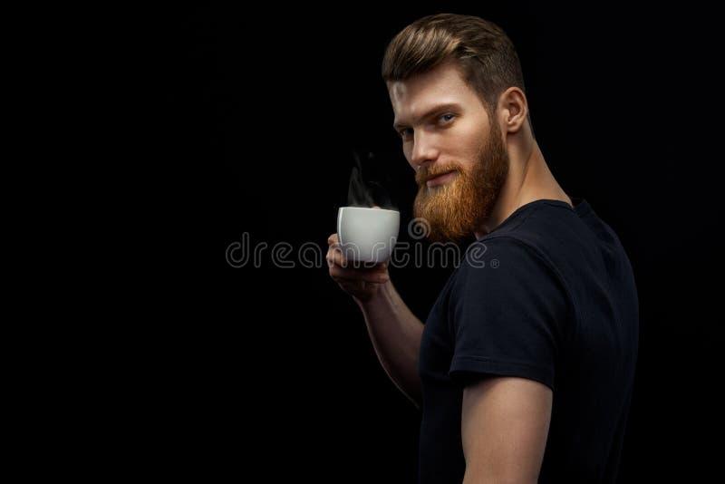 De gebaarde mens proeft koffie royalty-vrije stock foto