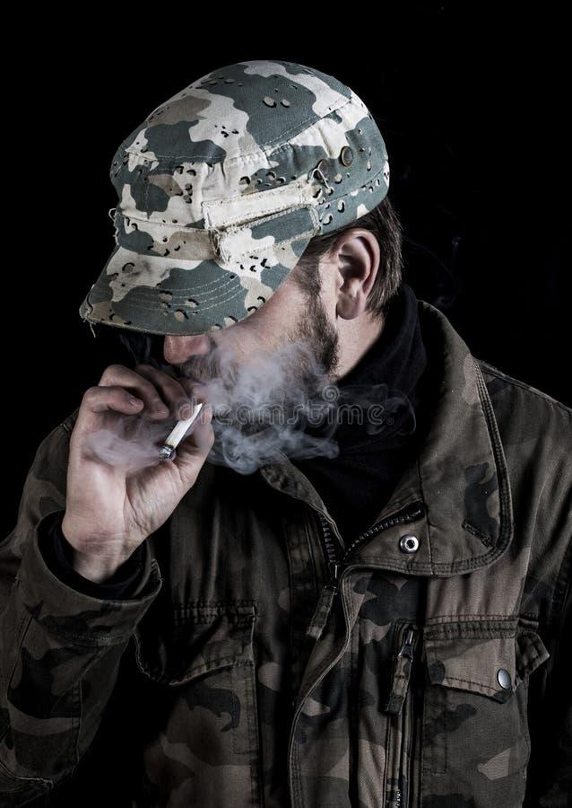 De gebaarde mens rookt een sigaret in Finland stock foto's