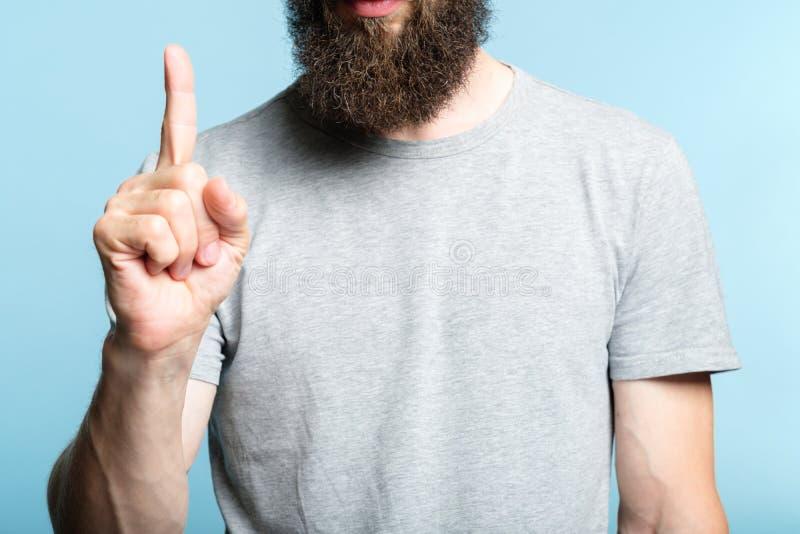 De gebaarde mens toont handnummer één tellend gebaar stock foto