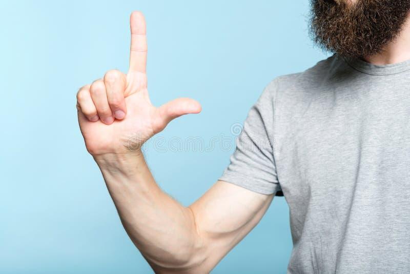 De gebaarde mens toont het kanongebaar van de handvinger stock foto