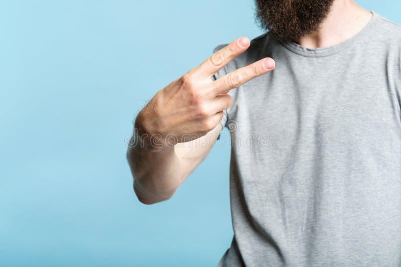 De gebaarde mensenhand toont nummer twee v-tekenstuk stock afbeeldingen