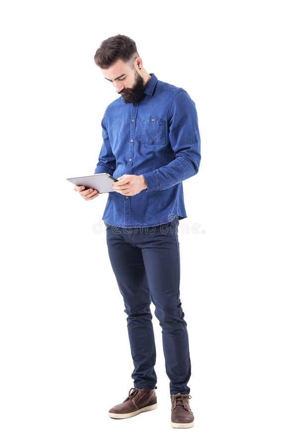 De gebaarde modieuze tablet van de bedrijfsmensenholding in beide handen die ebook lezen stock foto