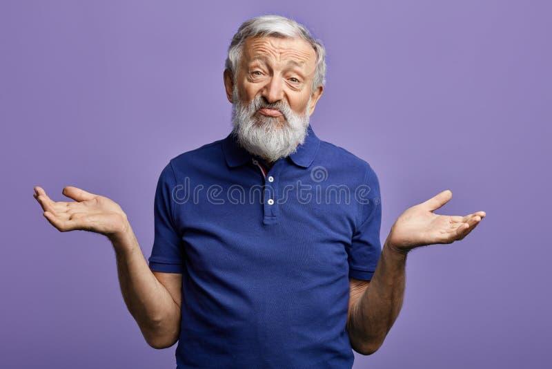 De gebaarde oude mens drukt clueless met opgeheven wapens uit bekijkend de camera stock foto