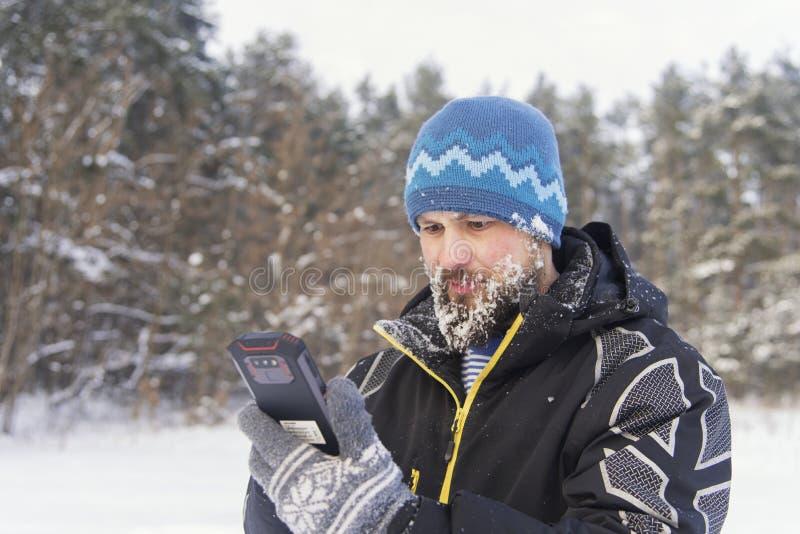 De gebaarde reiziger met verontwaardiging bekijkt de telefoon, aangezien er geen signaal van cellulaire mededeling is royalty-vrije stock foto's