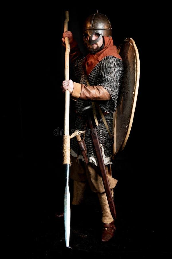De gebaarde strijder in het pantser en in de helm van Viking Age houdt een schild, een zwaard, een bijl en een lans stock foto's
