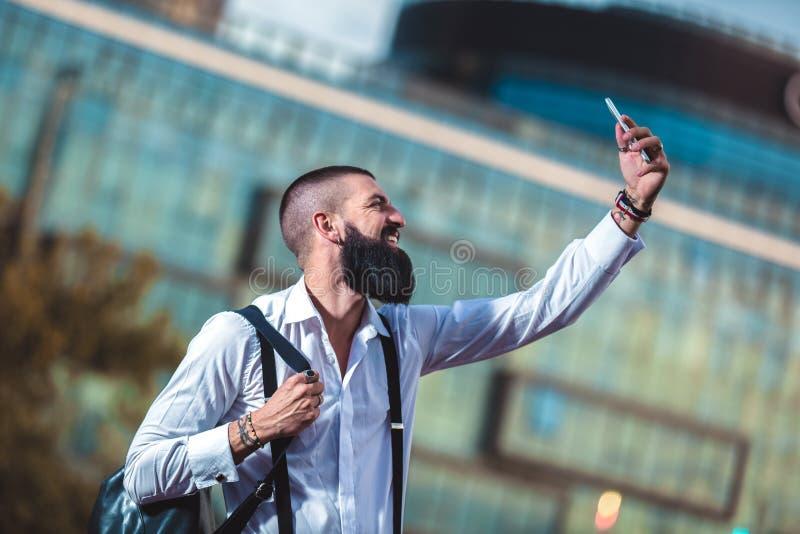De gebaarde zakenman maakt in openlucht selfie foto stock afbeelding