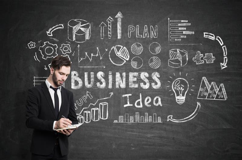 De gebaarde zakenman met een notitieboekje schrijft terwijl status dichtbij een bord royalty-vrije stock afbeelding
