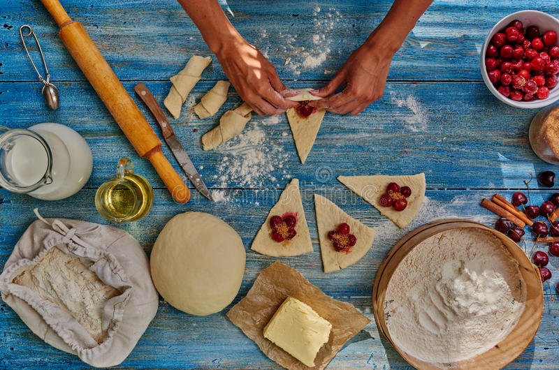 De gebakjechef-kok bereidt gebak met kersen voor stock fotografie