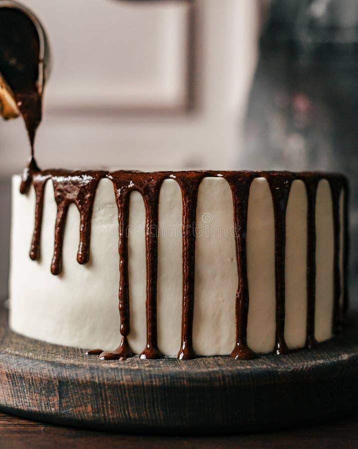 De gebakjechef-kok verfraait een chocoladecake Close-up stock foto's