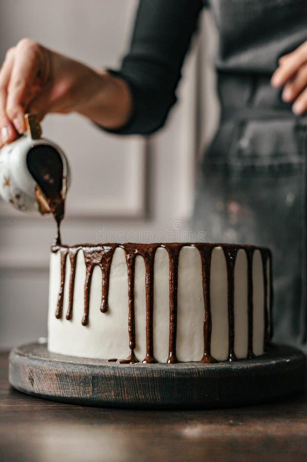 De gebakjechef-kok verfraait een chocoladecake Close-up royalty-vrije stock afbeelding